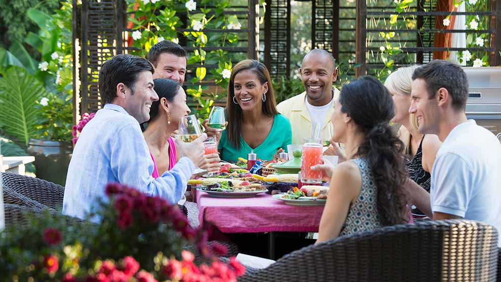 friends eating outside on a deck