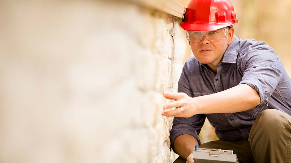 home inspector examines the home foundation