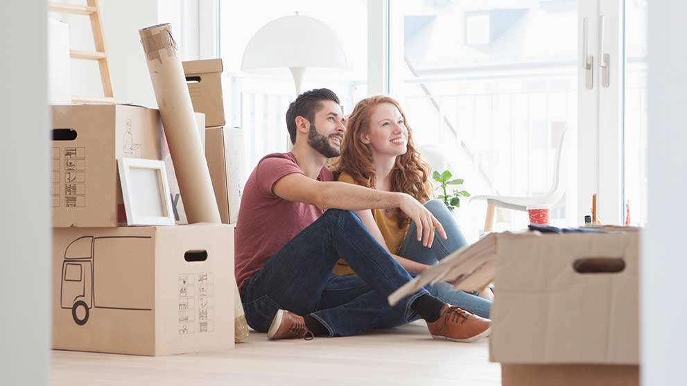 Young couple sitting in new home with boxes