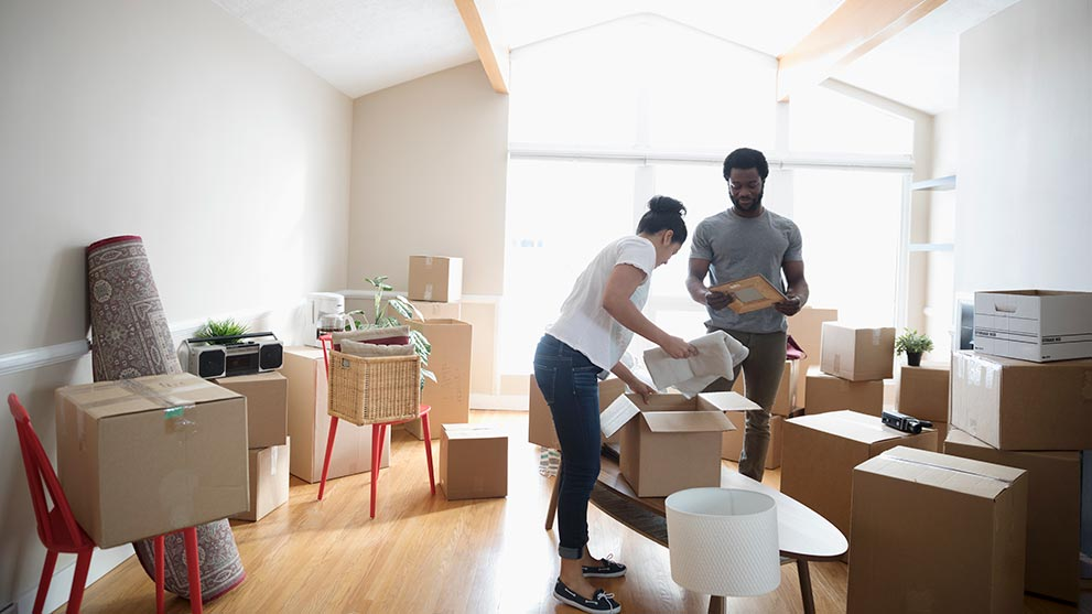young couple unpacks boxes in their new home