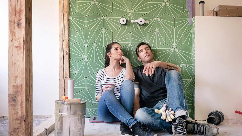 Young couple taking a break from renovating their bathroom