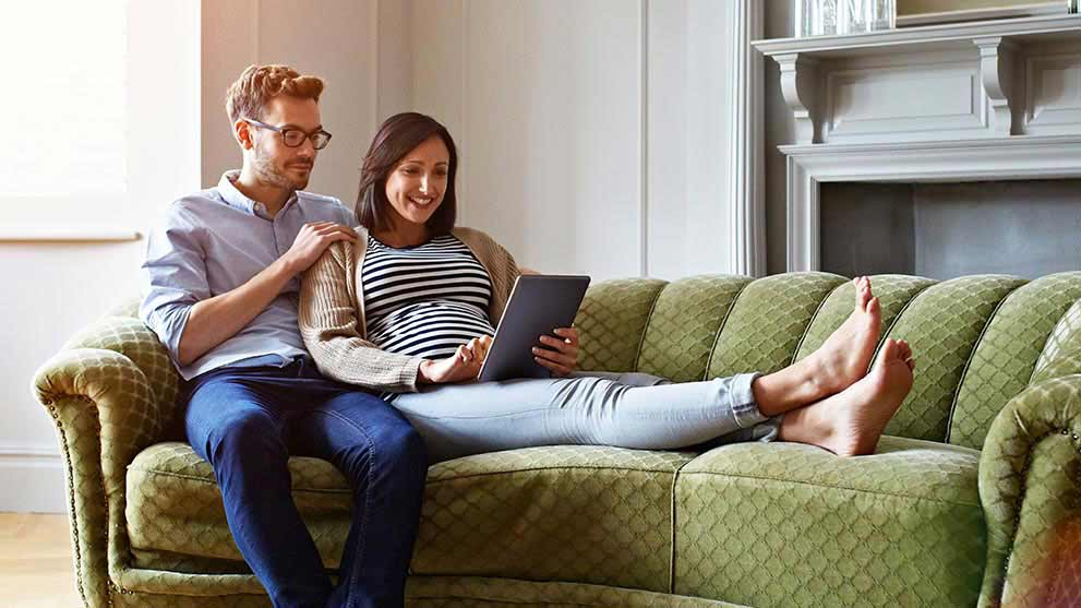 Pregnant couple sitting on a couch together looking at tablet
