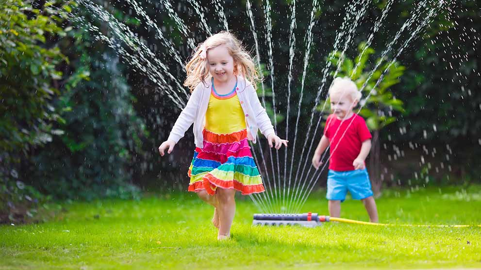 kids running through a lawn sprinkler