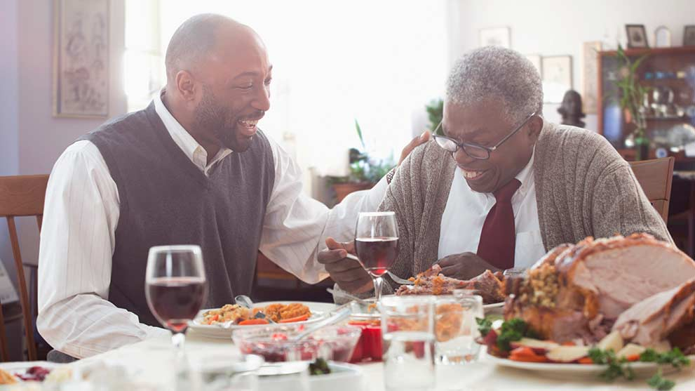 father and son enjoy thanksgiving dinner together