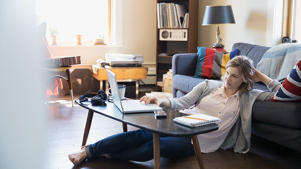 Woman using laptop on living room floor
