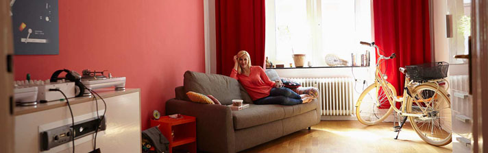woman sitting on her couch admiring her modern furnishings
