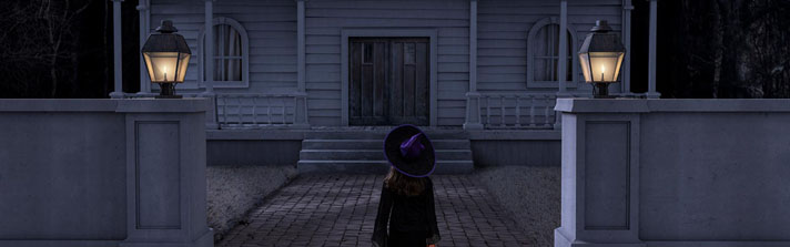 young witch looking at a haunted house