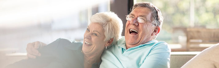 Mature couple laughing on the couch together