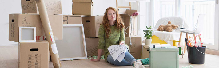 Young woman sitting on the floor with moving boxes.