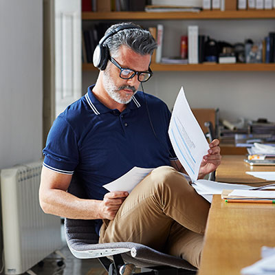 man reading papers at desk with headphones on