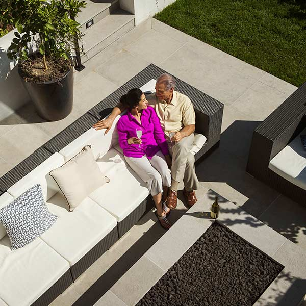 Older couple relaxing on modern backyard patio