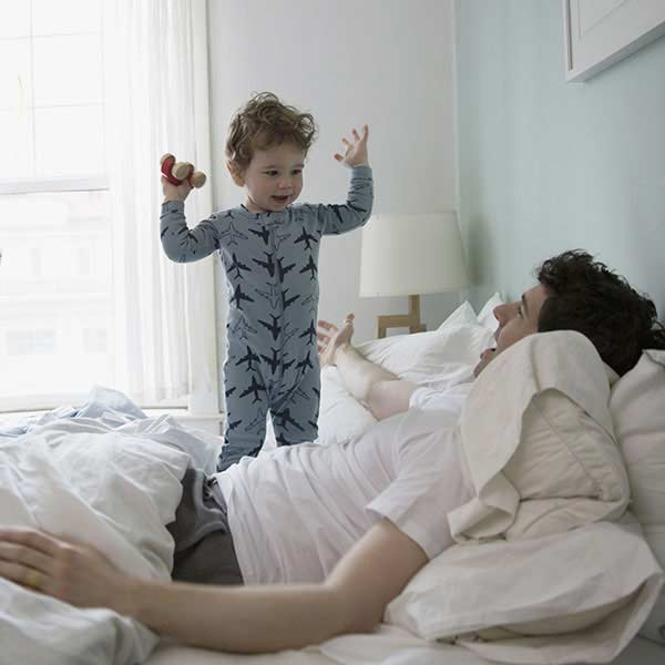 Little boy waking up his dad